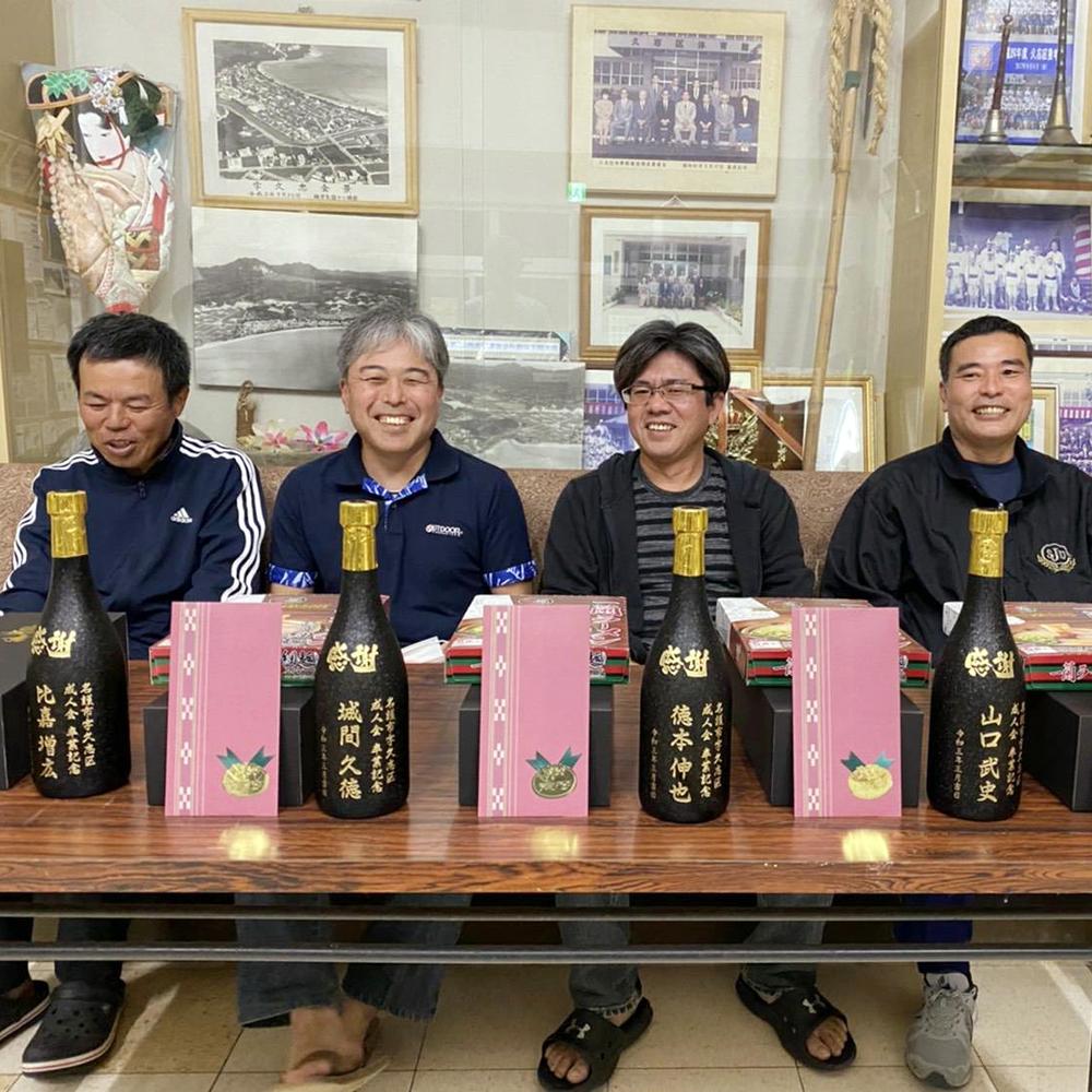 【画像】久志地区成年会の皆様と泡盛記念ボトル